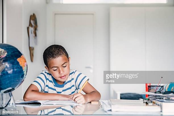 boy studying at table - homeschool ストックフォトと画像
