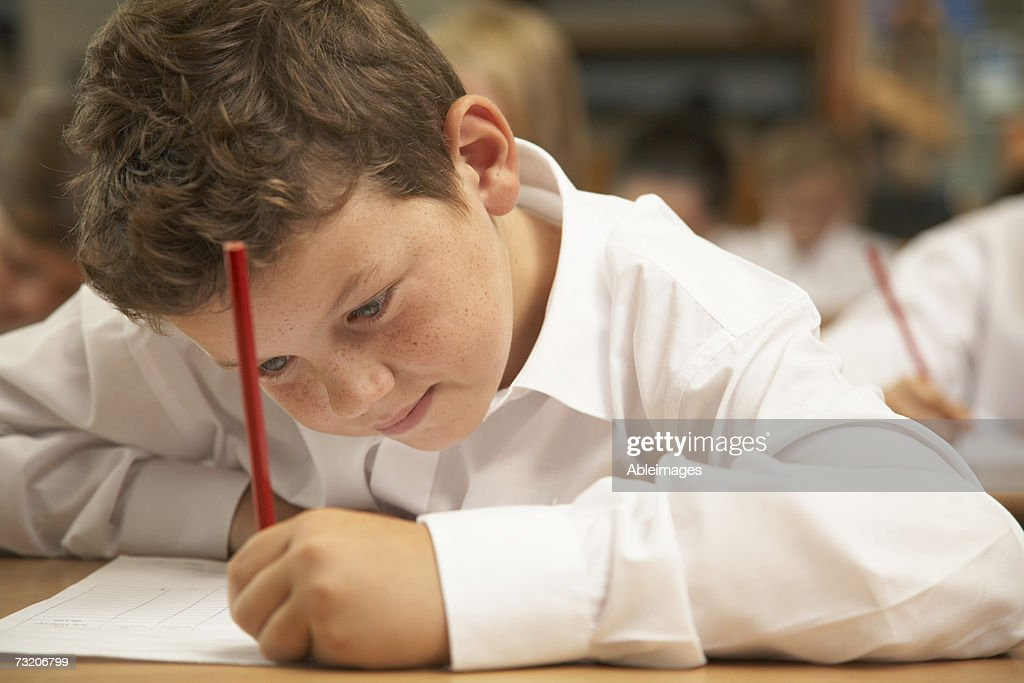 Boy (8-10) studying in classroom : Stock Photo