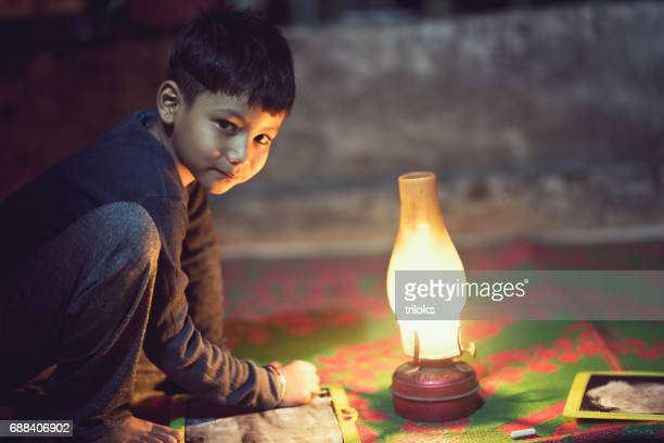 Boy studying in oil lamp