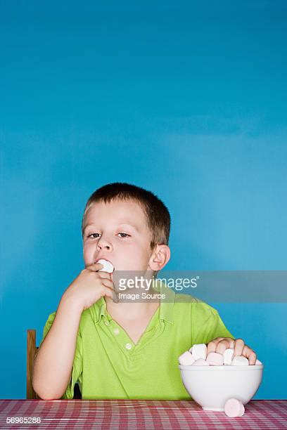 Garçon farce des marshmallows dans sa bouche
