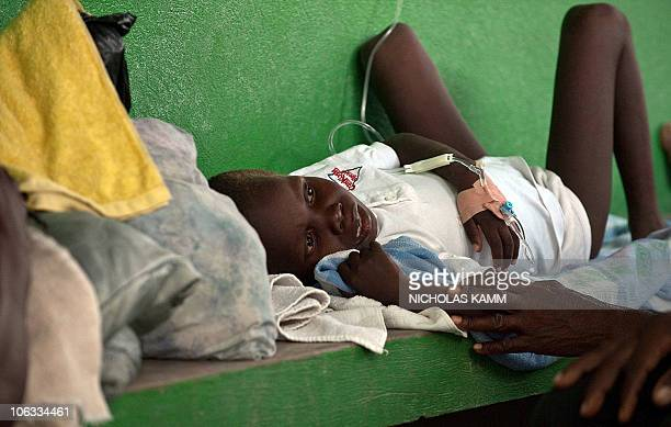 A boy suffering from dehydration and diarrhea is comforted by his father as he waits to be treated at the Charles Colimon Hospital in Petite Riviere...