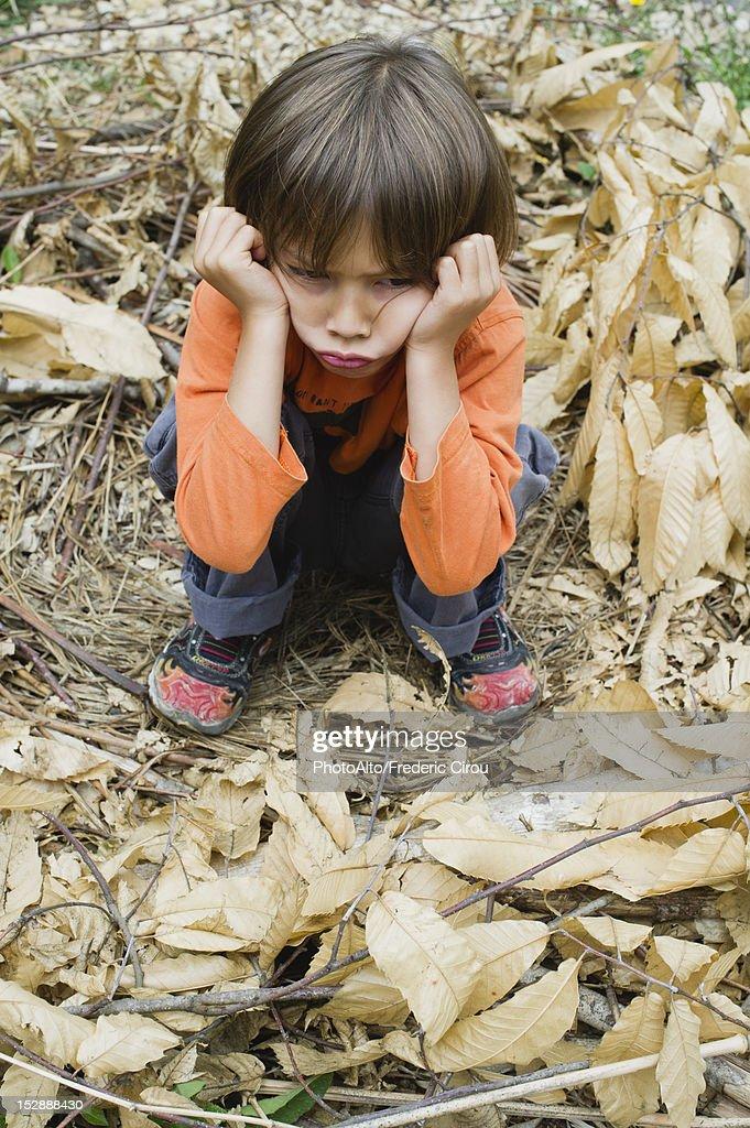 Boy sulking outdoors : Stock Photo