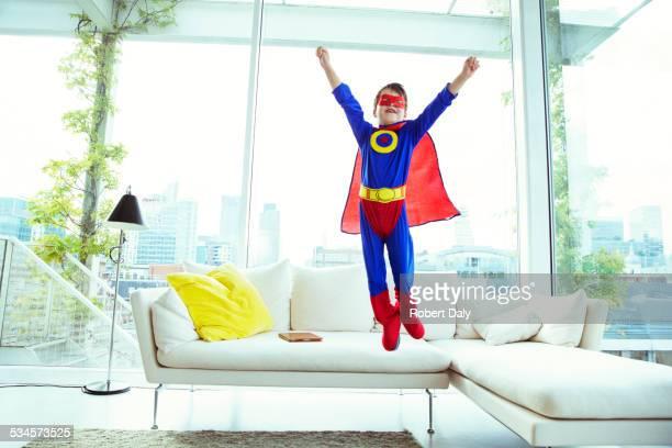 Boy superhero jumping off living room sofa