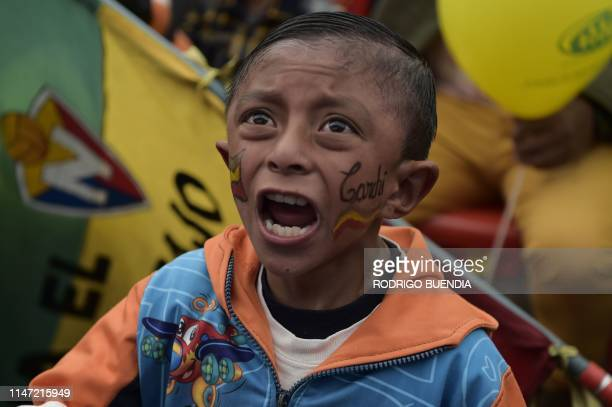 A boy supporter of Ecuadorean cyclist Richard Carapaz cheers as he follows the 20th and penultimate stage of the Giro d'Italia on a screen at the...