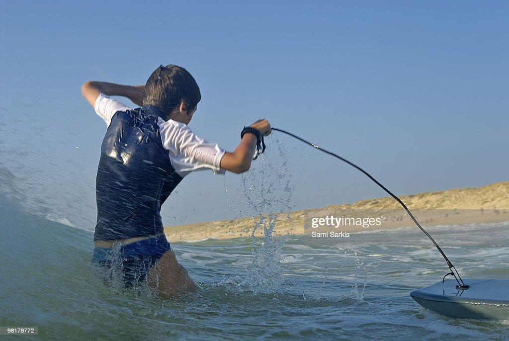 Boy (12) surfing and splashing in ocean waves : Stock Photo