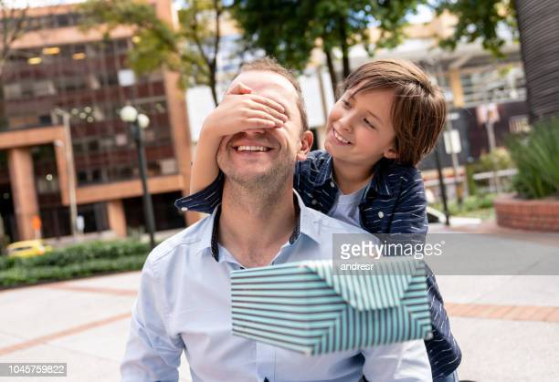 boy surprising his father with a gift for father's day - fathers day stock pictures, royalty-free photos & images