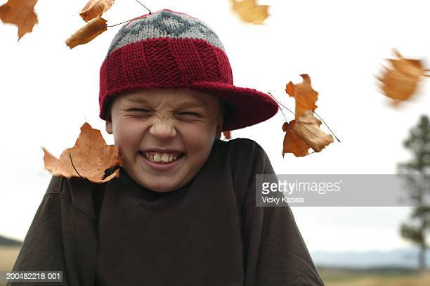 Boy (10-12) surrounded by autumnal leaves blowing in wind, grimacing