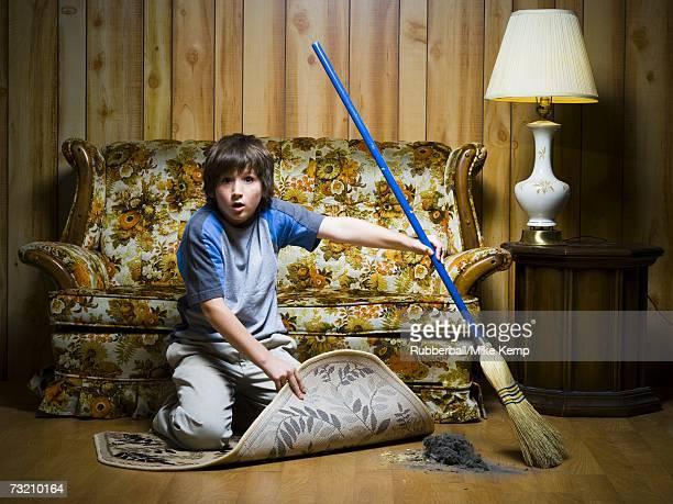 Boy sweeping dirt under rug