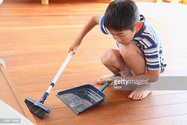 Boy sweeping floor with broom and dustpan