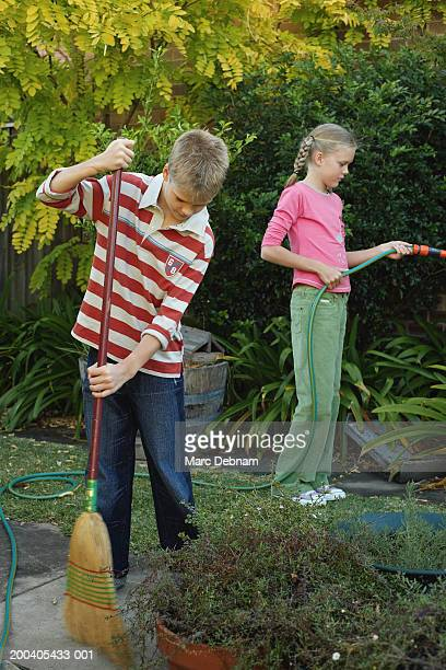 boy (10-12) sweeping path, twin sister using garden hose - red tube top stock photos and pictures