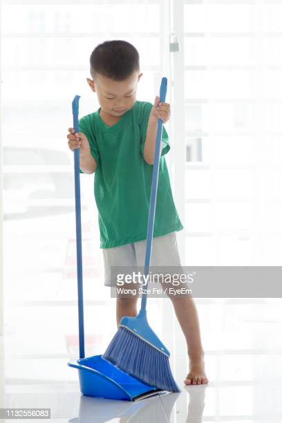 boy sweeping tiled floor at home - broom sweeping stock pictures, royalty-free photos & images