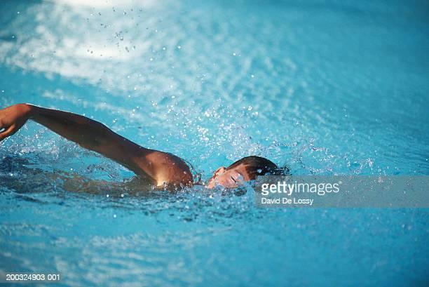 Boy (10-11) swimming in pool