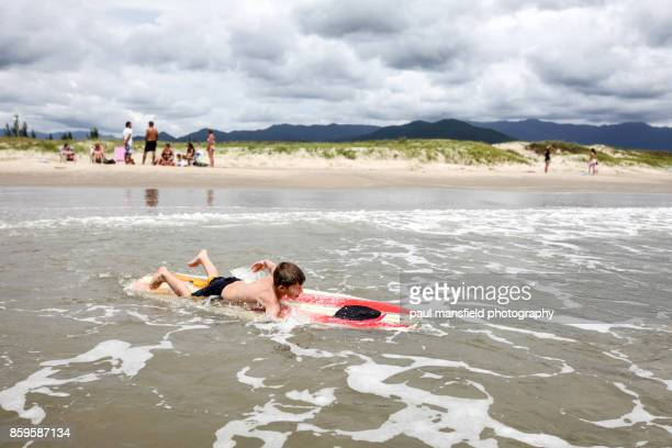 Boy swimming out on surfboard