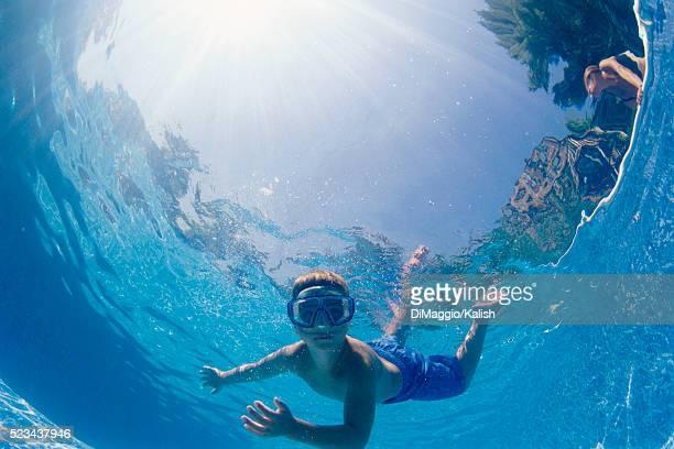 boy swimming underwater - 魚眼撮影 ストックフォトと画像