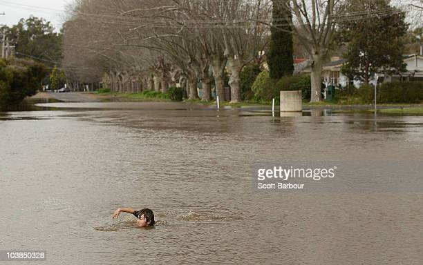 A boy swims down a flooded street on September 5 2010 in Benalla Australia Parts of the state were devastated by flood waters when heavy winds and...