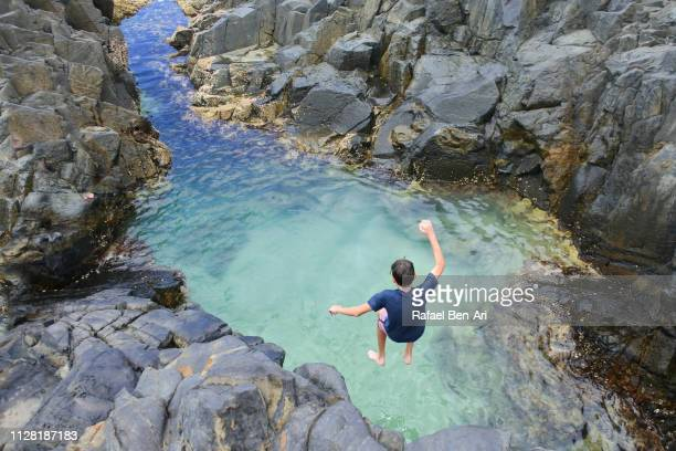boy swims in fairy pools, noosa heads - sunshine coast australia stock pictures, royalty-free photos & images