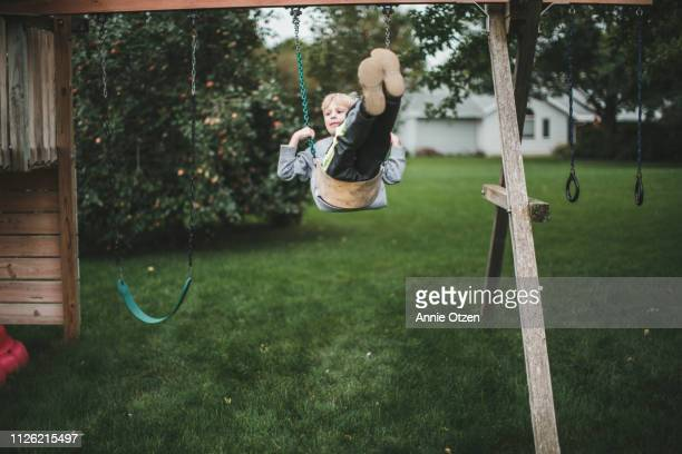 boy swing swinging on backyard swing - one boy only stock pictures, royalty-free photos & images