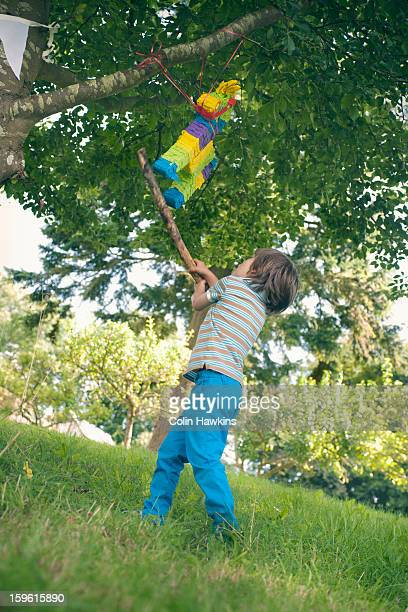 boy swinging at pinata at party - colin hawkins stock pictures, royalty-free photos & images