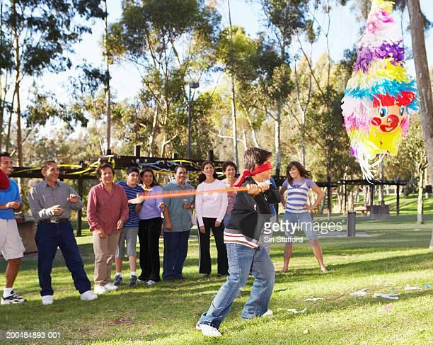 Boy (10-12) swinging at pinata in park