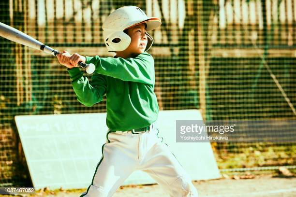 boy (6-7) swinging baseball bat at ball - sporting term stock pictures, royalty-free photos & images