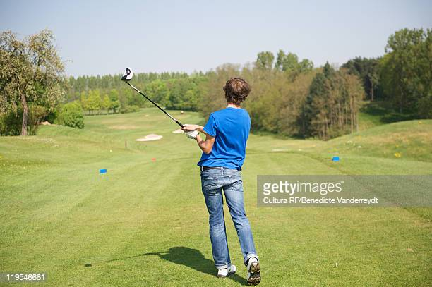 Boy swinging club on golf course