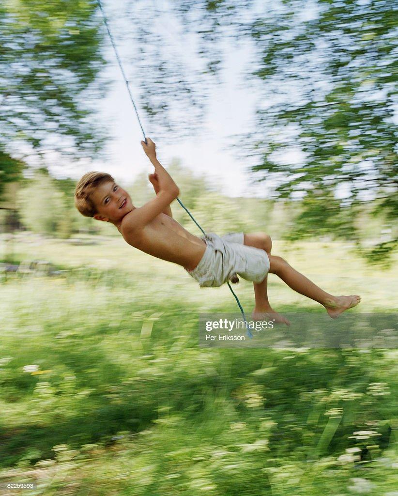 A boy swinging in a green garden. : Stock Photo