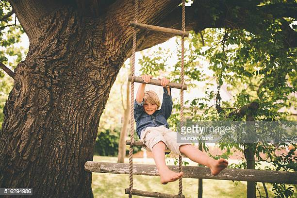 Boy swinging in a rope ladder from tree in park
