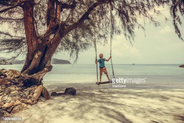 Boy  swinging on a beach