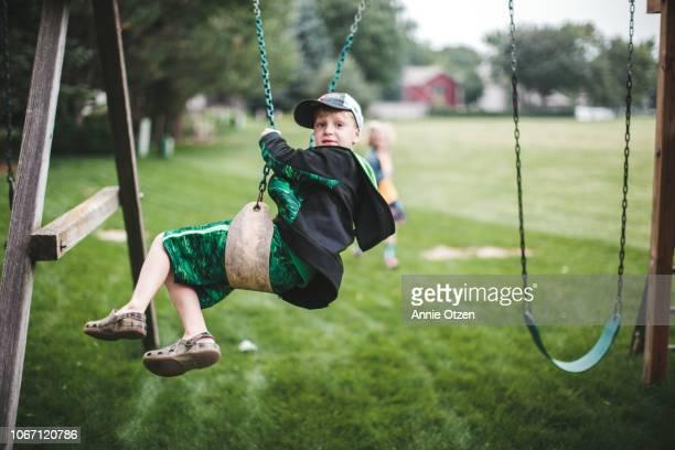 Boy swinging on backyard swing set