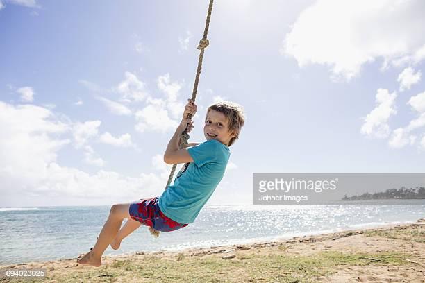 boy swinging on beach - schommelen bungelen stockfoto's en -beelden