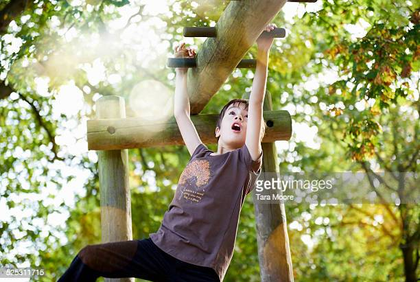 boy swinging on monkey bars in park