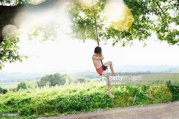 boy swinging on rope