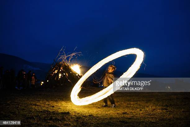 A boy swirls a fireball on February 22 2015 in the village of Lozen as Bulgarians are marking Sirni Zagovezni an Orthodox Christian holiday during...