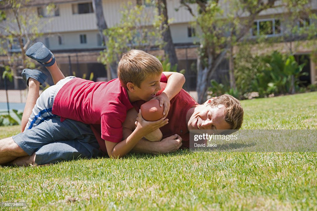 Boy tackling father playing American football in park : Stock Photo