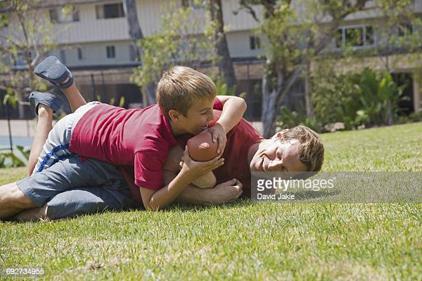 Boy tackling father playing American football in park