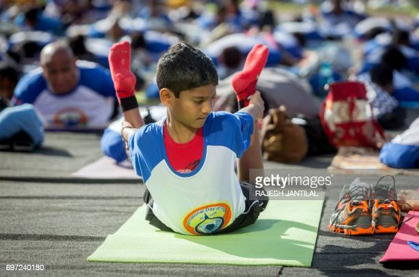 A boy takes part in a yoga session at the amphitheatre lawns at North Beach on June 18 2017 in Durban South Africa ahead of the International Day of...