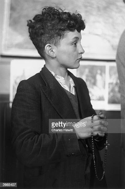 A boy takes part in the daily Rosary in a mining village of County Durham his prayer beads in his hand Original Publication Picture Post 5972...
