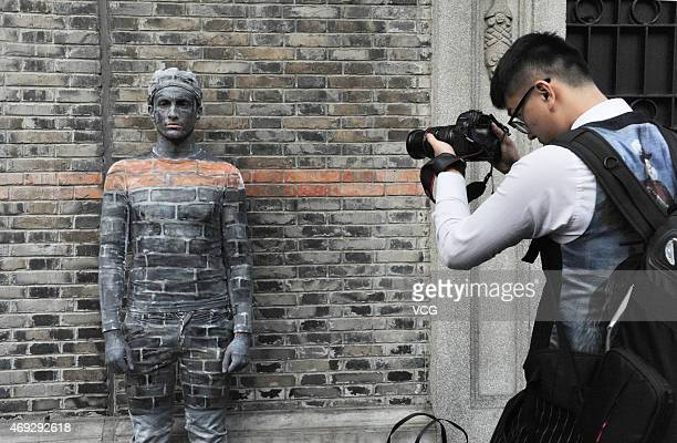 "Boy takes photos of a boy disguised as a wall near New World street on April 10, 2015 in Shanghai, China. A boy ""hides"" himself by being painted the..."