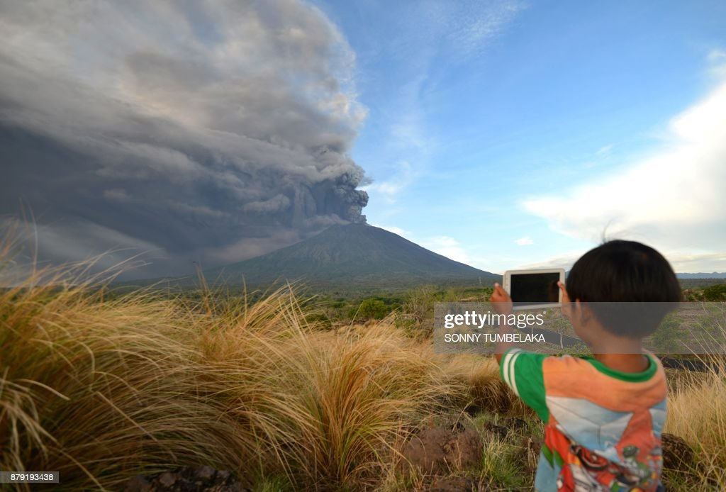 TOPSHOT - A boy takes pictures during Mount Agung's eruption seen from Kubu sub-district in Karangasem Regency on Indonesia's resort island of Bali on November 26, 2017. Mount Agung belched smoke as high as 1,500 metres above its summit, sparking an exodus from settlements near the mountain. /