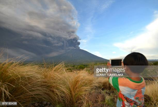 TOPSHOT A boy takes pictures during Mount Agung's eruption seen from Kubu subdistrict in Karangasem Regency on Indonesia's resort island of Bali on...