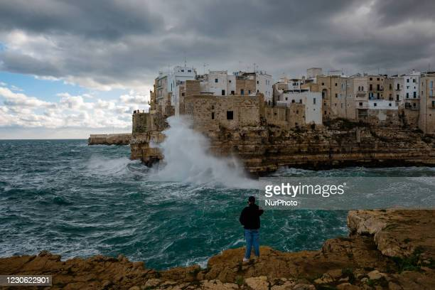 """Boy takes some photos with his smartphone of the storm on Lama Monachile in Polignano a Mare on January 16, 2021. The arrival of the """"Russian..."""