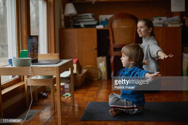 Boy takes yoga class with laptop at home with mother and arms outstretched