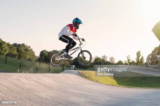boy taking a jump on his bmx - bmx cycling stock pictures, royalty-free photos & images