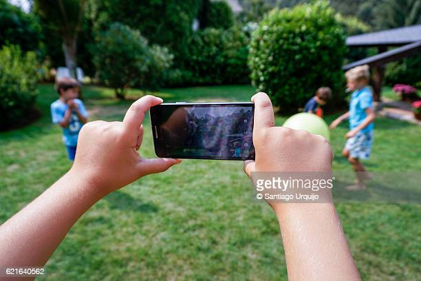 Boy taking a picture of friends with smart phone