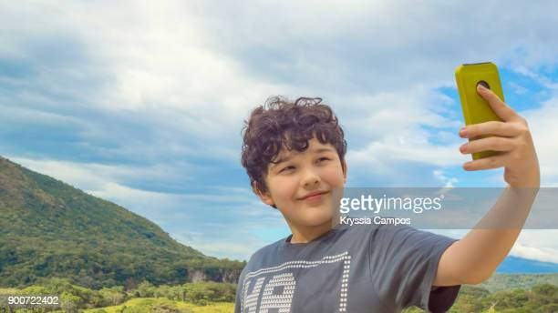 Boy taking a selfie with a smart phone outdoors in nature