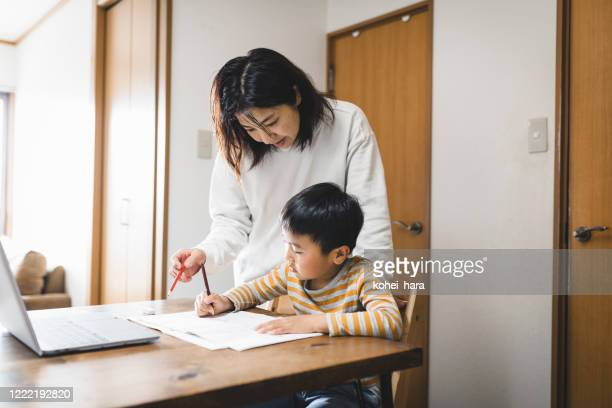 boy taking an e-learning course with laptop and his mother watching it - mindzoom 2 stock pictures, royalty-free photos & images