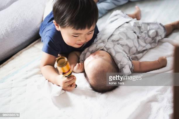 少年は、女の赤ちゃんの世話 - 兄弟 ストックフォトと画像