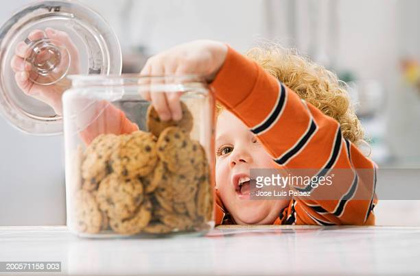 Boy (4-5) taking cookie from cookie jar, close-up