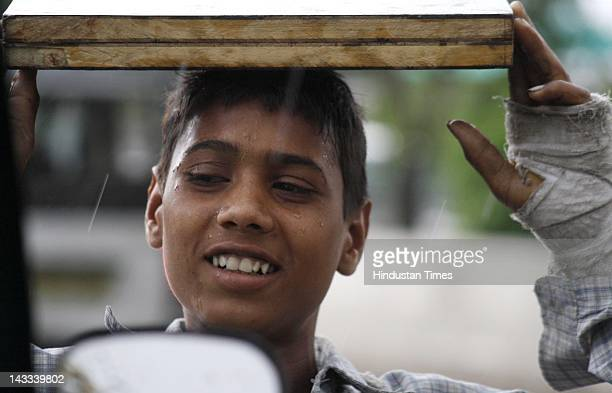 Boy taking cover under a wooden plank as it started raining suddenly after a hot day on April 24, 2012 in Noida, India.
