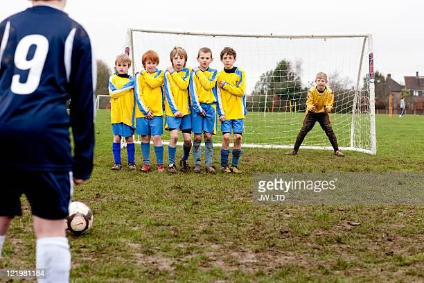 Boy taking free kick during football game